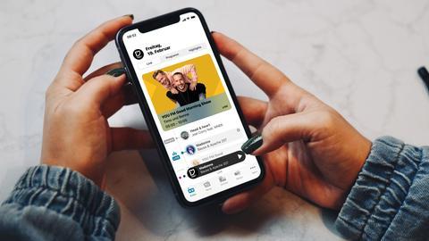 Smartphone mit der neuen YOU FM-App