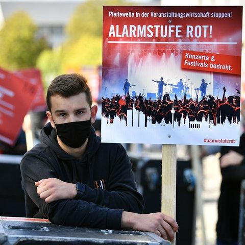 AlarmstrEin junger Mann demonstriert zusammen mit anderen Vertretern und Beschäftigten der Veranstaltungsbranche vor dem Thüringer Landtag.
