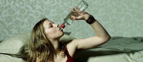 Junge Frau trinkt Alkohol