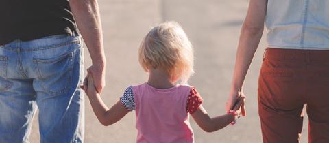 Zwei Frauen Hand in Hand mit einem kleinen Mädchen