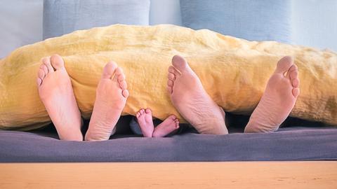 Füße einer Familie unter einer Bettdecke