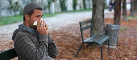 Mann sitzt auf einer Bank und putzt sich die Nase