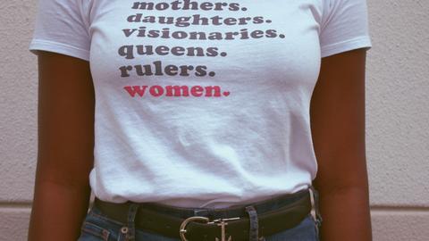 """Eine Frau trägt ein T-Shit mit """"Women""""-Schriftzug"""
