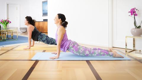 Zwei Frauen machen eine Stretching-Übung auf ihren Yogamatten auf dem Boden im Wohnzimmer.