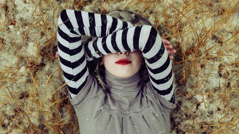 Eine Frau liegt auf dem Boden und bedeckt das Gesicht mit ihren Armen