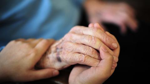Die Hand eines alten Menschen liegt in einer anderen Hand.