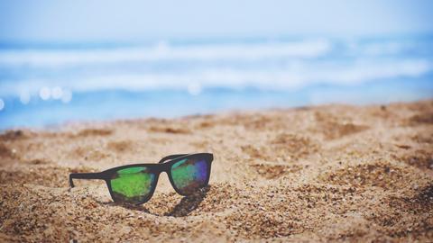 Eine Sonnenbrille liegt am Strand.