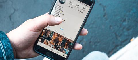 Jemand hält ein Smartphone in der Hand mit geöffneter Isntagram App