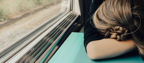 Eine Person hat den Kopf auf den Tisch gelegt und schläft