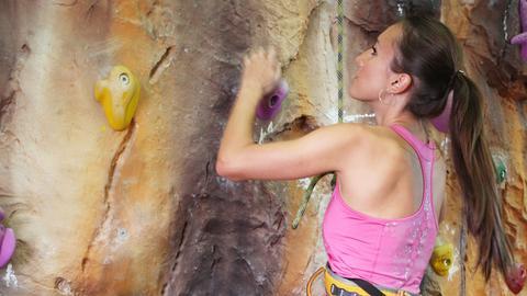 Eine Frau klettert an einer Kletterwand
