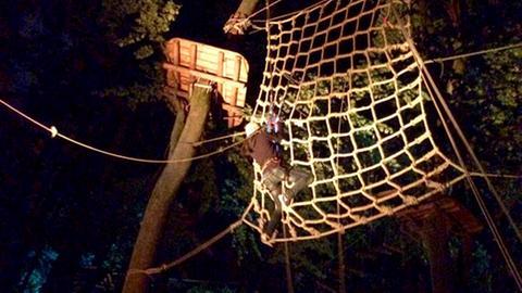 Ein Kletterer hängt nachts in einem Netz im Hochseilgarten.