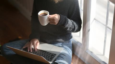 Frau mit Laptop auf dem Schoß