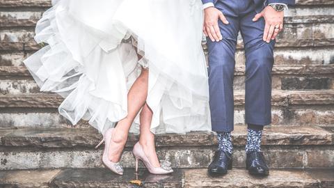 Die Unterkörper einer Braut und eines Bräutigams sind zu sehen.