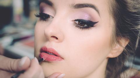 Eine Frau wird professionell geschminkt.