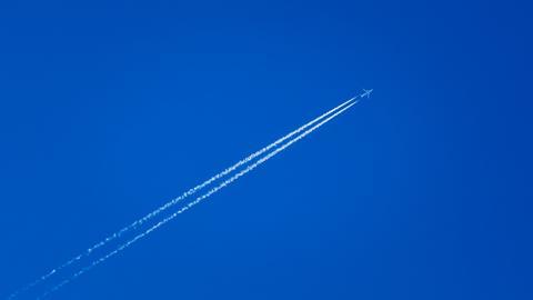 Ein Flugzeug hinterlässt einen Kondensstreifen am Horizont.