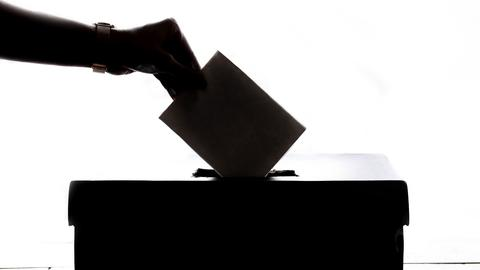 Ein Wahlzettel wird in eine Box geworfen