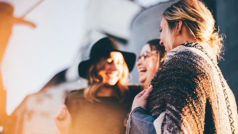 Drei junge Frauen lachen miteinander