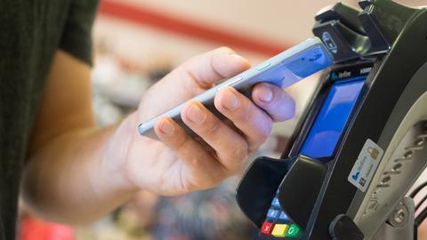 Ein Mann bezahlt in einem Laden mit seinem Smartphone