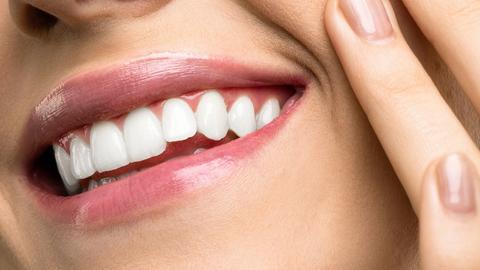 Eine lächelnde Frau zeigt strahlen weiße Zähne.