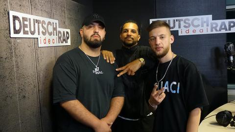 Drei in schwarz gekleidete Männer stehen in nebeneinander einem dunklen Studio. Sie legen die Arme umeinander. An den Wänden ist das Logo von Deutschrap ideal.