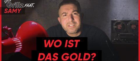 Ein Mann sitzt in einem dunklen Raum und wird von einer roten Lampe angeleuchtet. Darunter steht in roten Großbuchstaben: Wo ist das Gold?