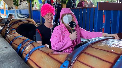 Eine Frau mit pinker Jacke und Kapuze auf und ein Mann im Neoprenanzug mit roter Lockenperücke sitzen in einer Achterbahn.