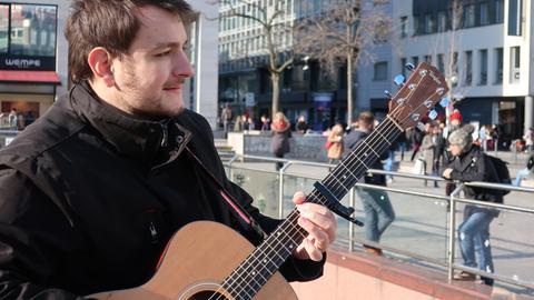 Adrian macht Straßenmusik auf der Frankfurter Zeil