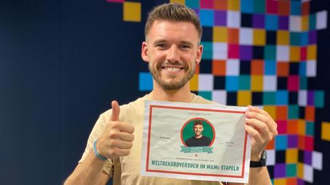 Ein Mann mit einem beige-farbenen T-Shirt steht vor einer bunten Wand. Er lächelt und zeigt mit der einen Hand einen Daumen nach oben. Mit der anderen Hand hält einen Zettel hoch, auf dem steht: Fast geschafft! Weltrekordversuch im M&Ms-Stapeln.