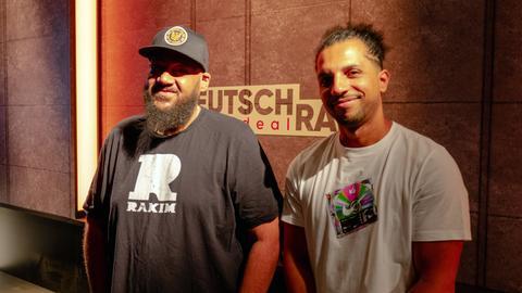 """Moses Pelham und Moderator Simon vor einer Wand mit dem Logo """"Deutschrap ideal"""""""
