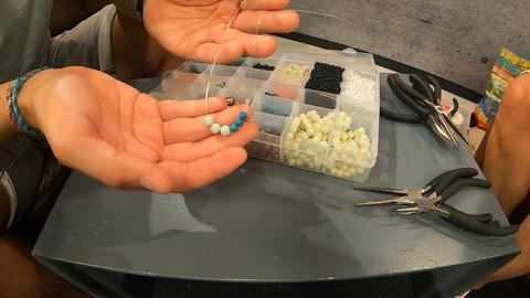 Zu sehen sind ein transparenter Kasten mit verschiedenen Fächern, in denen diverse Perlen liegen sowie eine Hand, die sechs Perlen auf eine Schnur auffädelt.